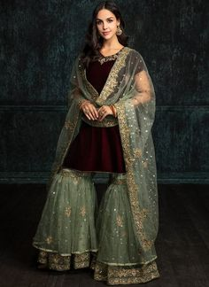Wine and Mint Velvet Gharara Suit features a velvet kameez with santoon inner, net gharara with santoon inner and embroidered net dupatta. Embroidery work is completed with zari, sequins and stone work embellishments. Pakistani Wedding Outfits, Pakistani Dresses, Bridal Outfits, Pakistani Gharara, Pakistani Bridal Wear, Designer Party Wear Dresses, Indian Designer Outfits, Indian Designers, Indian Dresses