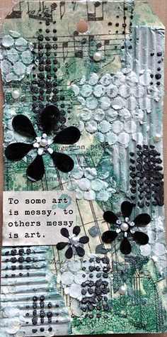 Distress inks and dreamweaver embossing paste along with flowers cut from an old book and coloured with black distress paint