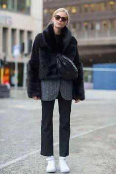 Look com calça alfaiataria, blazer sob faux fur coat e tênis branco.
