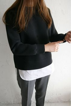 Minimal + chic: Dress down a sharp pair of slacks with an untucked white shirt and black sweatshirt
