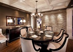 A light, neutral cultured stone accent wall adds texture to this beautiful traditional dining room. A paneled ceiling is a beautiful and bright contrast to the warm neutral color scheme. A chandelier illuminates the dark wooden table and the sleek lines of the cream colored chairs. A buffet matches the rich wood of the table and supports to table lamps adding extra ambiance.