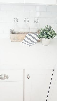 Refinished old tool box, Ikea glass bottles, Ikea striped cup towels, Ikea hand towel, cute dish towels, Ikea faux plants, subway tile with light gray grout, white subway tile, white kitchen, quartz countertop that looks like marble
