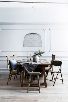 Cozy Scandinavian dining space with a woven pendant light, light gray walls, and a simple rustic dining table with mis-match chairs