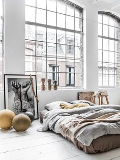 Loft, windows, bed, artwork, wood floor, white walls, photograph, decorative objects