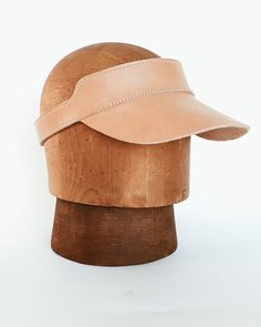 Soft light Veggie Tan Leather Visor that will darken with age and sun designed and handmade by Right Tribe in Manhattan Beach CA. Note: Color variation and minor markings, are characteristic of Vegetable Tan Natural leather. it starts as a pale pink and tans over time and exposure to sun.