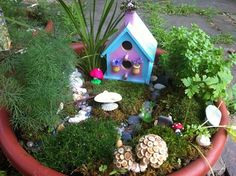 """""""This is Raineys creation. I cant say that it is totally complete as I know things will be added all year long. Rainey loves to twine nature and makes crowns and furniture and tiny fairies. So those will come and go. But for now her garden has a lovely fairy home. Painted pink, purple and blue with flowers painted on the side. She also included two flower pots with fresh flowers and a woven chimney crown. Included in the grounds are mosses, grasses and herb plants."""