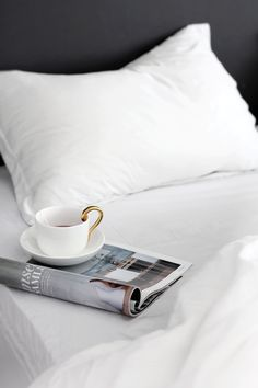 White Bedsheets + Gold Handle Coffee Cup + Magazine Reading