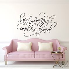 """""""Have Courage and Be Kind"""" vinyl wall quote in black on a beige wall behind a vintage pink couch with white satin pillows. The quote is written in all lowercase in handwritten, chic text. Vinyl Wall Quotes, Vinyl Wall Stickers, Wall Decals, Wall Art, Diy Wall, Pink Couch, Have Courage And Be Kind, In This House We, Co Working"""