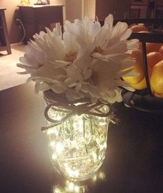DIY Mason jar with fairy lights. Copper twinkle/fairy lights inside of a Mason jar. Fake flowers of your choice and some burlap twine to finish it off. These fairy lights are battery operated so very easy to turn on and off. Home decor DIY.