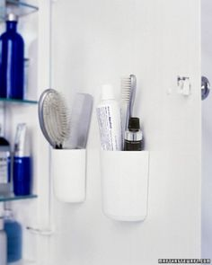Combs, brushes, and toothpaste take up considerable space when laid horizontally on a shelf. Flat-backed, self-adhesive cups on the inside of the cabinet door hold them more efficiently. Before pressing the cups in place, line them up between the shelves. To ensure the door can close, put thin items on the shelves in the spots where the cups will take up some space.