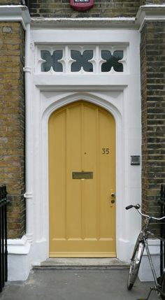 A cheerful yellow front door. We also love the flower windows above!