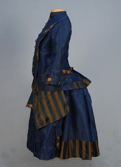 YOUNG GIRL'S SILK BUSTLE DRESS, 1870's. Blue faille 2-piece, having peplum and apron front of blue and maize striped silk, decorated with maize and olive silk floral embroidery, front closing with ten stamped and enameled brass buttons, faux flap pockets, back button and cord detail.