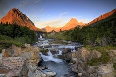 Swiftcurrent Falls. Swiftcurrent Falls is fed by Swiftcurrent Lake in the Many Glacier area of Glacier National Park. This is an early September morning, with the sun just beginning to come up illuminating Grinnell Point on the right, Swiftcurrent Mountain center and Mt Wilbur on the right... by Joseph Urgo on 500px.