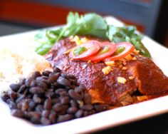 Braised Pork Enchiladas. This cheesy, creamy meal comes with red sauce, black beans and Spanish rice.