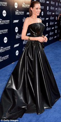 Black magic: Angelina looked incredible in her Versace black leather strapless gown, which had ruched detailing and a long leather train.