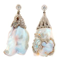 """Gorgeous Art Deco earrings featuring two large natural saltwater baroque pearls. The pearls come with GIA Natural Pearl Identification Report. One pearl is white, the other one is white/grey. The pearls are set in platinum and accented with rose cut diamonds. They are 1.5"""" long (4 cm) and 5/8"""" (1.7 cm) wide at the bottom."""
