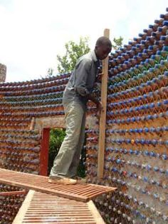 """Great plastic bottle project in Africa. """"Filled plastic bottles of sand are stacked into layers and bonded together by mud and cement, and held together by a network of strings to provide extra support to the structure. The structure is fire proof, bullet proof, earthquake resistant, and highly insulated. The builders claim the sand-filled bottles are stronger than ordinary cinder blocks. This home requires an approximate 14,000 bottles . . ."""""""