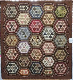 """""""Sisterhood"""" by Catherine Butterworth, photo by Katrina Hadjimichael. 2013 Sydney Quilt show. Made of the Seven Sisters block, every diamond in the stars was """"fussy cut"""" from a different fabric and each hexagon block was a different colour. As if that were not enough, Catherine appliqued 510 circles in the sashings.."""