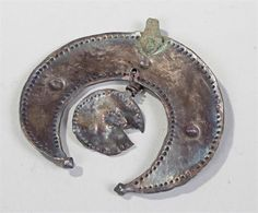 Viking silver lunate and disc pendant, crescent silver sheet with soldered on stud terminals, inner and outer egdes defined by lines of small punched dots, three larger bosses punched symmetrically within the body of the moon, suspended within the lunate is a silver disc, possibly Viking harness decoration, metal analysis supplied, ex Pummell collection, 6cm wide