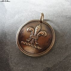 Fleur De Lis pendant from antique British livery button impression.  This listing is for one bronze pendant. Fleur-De-Lis  As a stylized form of the lily flower it represents sweetness, purity and light.  The antique button used in creating this pendant dates back to the 19th Century England. NOTE: * this listing is for one pendant * size is about 22mm across * pendant is made of solid bronze * no frills - shipped with no meaning card, no gift packaging * the pendant you will receive is…