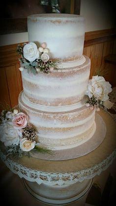 Semi naked wedding cake with handmade sugar flowers and fresh mini flowers.