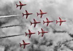 The 'Red Arrows' formation, Blackpool Airshow - Nine 'Red Arrows' in a V formation, in full flight during the Blackpool Airshow. The red of their body pops out against a black & white background of clouds.