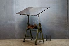 Germany, c.1930s. Vintage Marabu German Auto Plant Engineering Design Department Mechanical Lift Drafting Table. Cast Iron, Highly Adjustable (Lever for Angle, Pedal for Height), Old Growth Wooden and Black Micarta Drawing Deck. Small Storage and Drawing Tool Ledge.  W: 60 x D: 32 x H: 71 In. *(H: 71, Represents the Highest Adjustment)