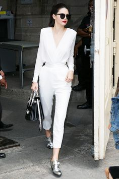 Kendall Jenner wears a white belted jumpsuit, Saint Laurent leather bag, and metallic Barbara Bui oxfords