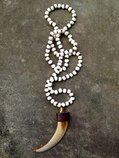 """Bone knotted on silk with wild boar tusk pendant. Unless otherwise specified it will be approximately 36"""" in length."""