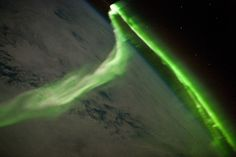 """Aurora Australis From Space    Photograph courtesy NASA and NASA Earth Observatory    """"Even for astronauts, this May image was a rare sight indeed: an aurora hovering over the southern Indian Ocean.    Auroras occur when charged particles from the sun collide with Earth's upper atmosphere, causing atoms of oxygen and nitrogen to gain energy and then release it in the form of light.    Auroras typically are visible only near Earth's Poles, where magnetic field lines channel charged particles…"""