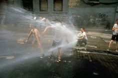 Children cool off in the spray of a fire hydrant on a New York City street, 1969 by Vernon Merritt III.
