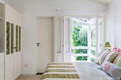 Quarto em casa de praia tem roupa de cama com mix de estampas e decoração clean.