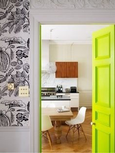 Unexpected bright doors that lead into a calm kitchen with white cabinetry & chairs and hardwood floors.
