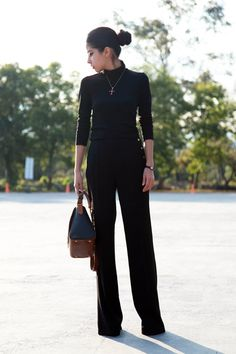 black pants and black turtleneck sweater with heels and a pendant necklace