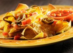 Are Nachos Mexican? Yes and No - but They Definitely are Delicious: A plate of delicious nachos topped jalapeños slices and chopped tomato