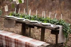 Weddind table setting with white plates and green glasses decorated with white candles, green leaves and eucalyptus outdoors