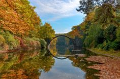 Rakotzbrücke - Nestled among the verdant foliage in Kromlau, Germany's Kromlauer Park, is a delicately arched devil's bridge known as the Rakotzbrücke which was specifically built to create a circle when it is reflected in the waters beneath it.
