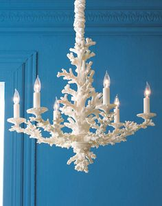 A coral chandelier against a blue wall.