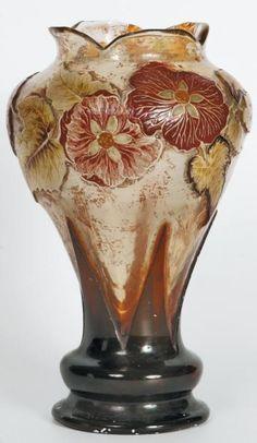 Émile GALLÉ (1846-1904) Vase de forme florale à corps balustre épaulé et col quadrilobé découpé à chaud sur pied balustre à deux renflement et feuilles dressées. Épreuve en verre fumé jaune à décor de cyclamen gravé en réserve à l'acide, émaillé à chaud et rehaussé de dorure. Signé. Haut. 27 cm