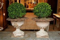 Gorgeous pair of early 19th century cast iron urns in old pink paint.