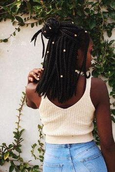 backshot of woman with medium sized box braids styled into a half up half down bun hairstyle