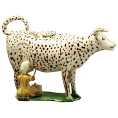 Cow creamer English Pottery Figure of a Cow in the Form of a Creamer Late 18th Century; profusely decorated with brown spots  & standing on a thin base, a feature much in vogue on these figures from the late 18th century