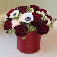 one dozen Black Baccara roses, Peach Vision spray roses, anemone, and seeded eucalyptus in a six inch cylinder vase wrapped with burgundy silk