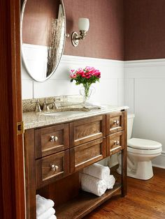 Brown granite, with its creamy beiges and coffee-hued specks, prevents a furniture-like vanity from appearing heavy. The countertop material is dark enough to pop off white wainscoting, yet stays in sync with this bathroom's other surfaces, including rich wood flooring and grasscloth-covered upper walls./