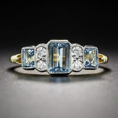 A trio of bright and beautiful, deep pastel-blue emerald-cut aquamarines, together weighing 1.39 carats, alternate with pairs of bright white sparkling diamonds in this sleek and stunning ring, crafted in London, England in homage to 1930s vintage Art Deco style. Crafted in two-tone 18 karat gold,with hallmarks inside the size 7 ring shank.
