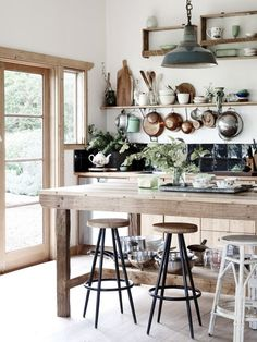 Kitchen featuring exposed wood, copper accents and big windows letting the light shine in.