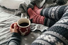 A woman drinking coffee in bed with cozy winter pajamas on