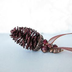 This pine cone necklace features a pendant made with a real pine cone coated with a shimmery garnet colored lacquer. Small rounds of garnet and a tiny copper leaf charm adorn the top of the pendant. T