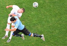 England On Brink Of World Cup Elimination After 2-1 Loss To Uruguay - Uruguay's forward Luis Suarez (FRONT) challenges England's defender Gary Cahill for the ball during the Group D football match between Uruguay and England at the Corinthians Arena in Sao Paulo on June 19, 2014, during the 2014 FIFA World Cup.