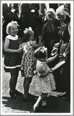 De prinsesjes nemen de honneurs waar voor hun afwezige ouders en begroeten de ouden van dagen die in klederdracht naar paleis Soestdijk zijn gekomen. 1946 #Saksen